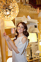 Happy young woman looking away while standing in lights store