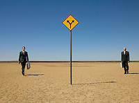 Two businessmen with briefcases walking towards road sign in desert full length