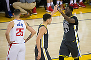 Golden State Warriors guard Klay Thompson (11) high fives Golden State Warriors forward Draymond Green (23) during a NBA game against the LA Clippers at Oracle Arena in Oakland, California, on February 22, 2018. (Stan Olszewski/Special to S.F. Examiner)
