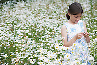 Girl (7-9) in meadow full of flowers