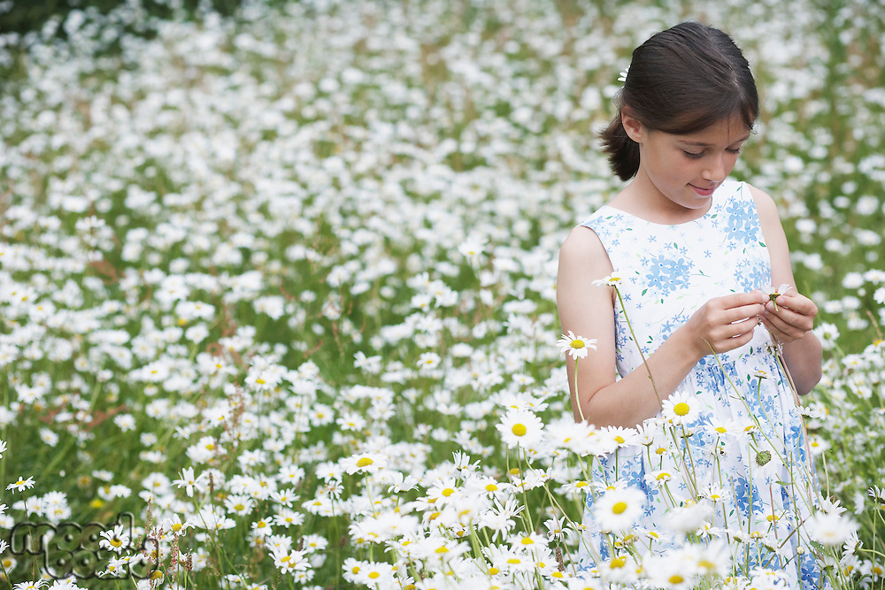 Girl (7-9) in meadow full of flowers