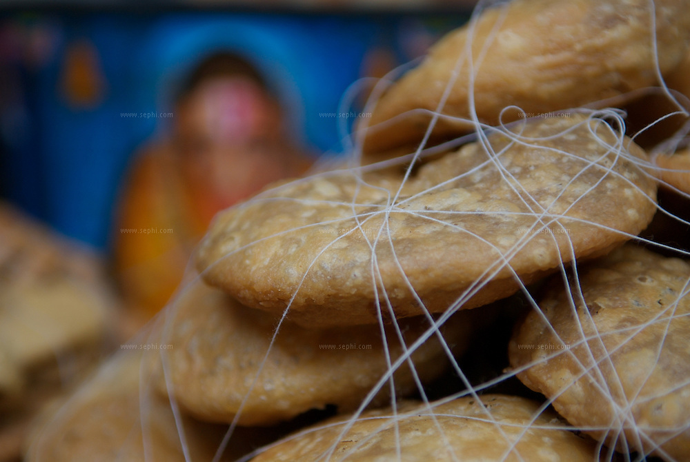 Kachoris rapped in a light string and a picture of the God Hanuman. Old Delhi, March 2007