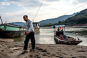 The captain of a sand dredging boat heads to shore in the evening in Simaogangzhen, Yunan, China.  The dredged sand is sold locally and to large scale construction sites in nearby major cities such as Kunming and Jinhong.