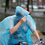 Foto: David Rozing Nederland Rotterdam 27 juli 2013 20130727 Noodweer in Nederland, zware onweersbuien teisteren Rotterdam. In korte tijd valt er een enorme hoeveelheid regenwater. Dame op fiets in regenpak, poncho. Foto: David Rozing