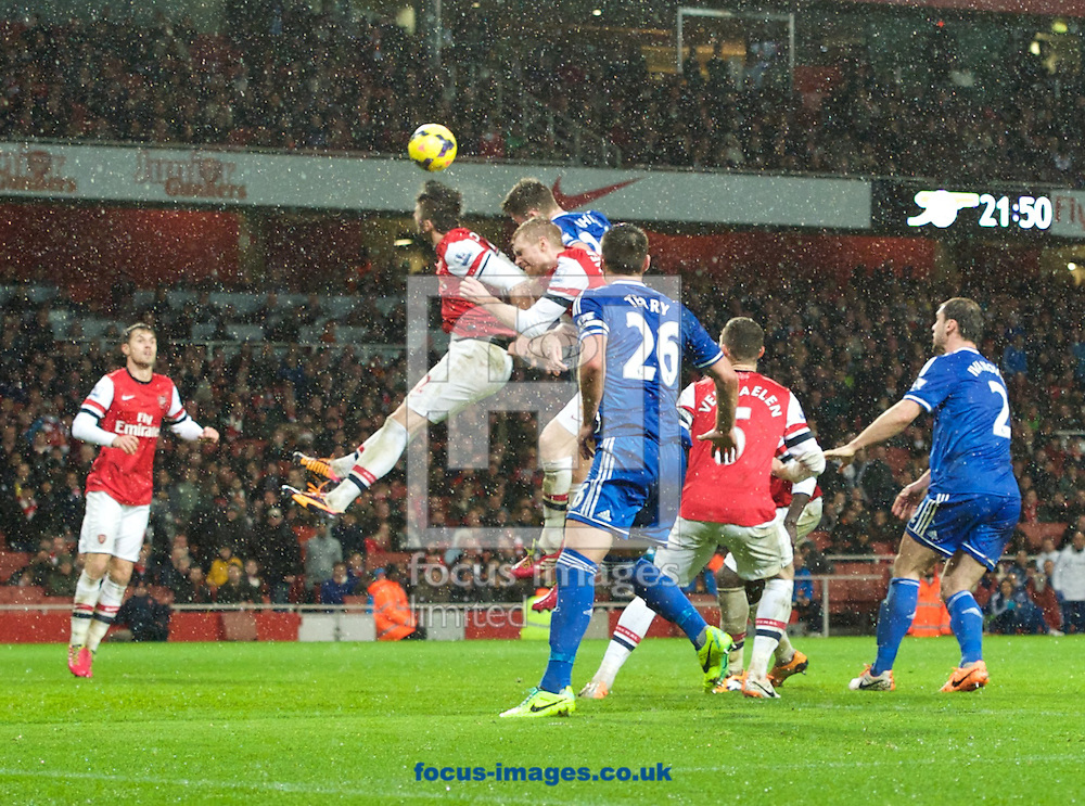 Picture by Alan Stanford/Focus Images Ltd +44 7915 056117<br /> 23/12/2013<br /> Olivier Giroud of Arsenal puts in a defensive header during the Barclays Premier League match at the Emirates Stadium, London.