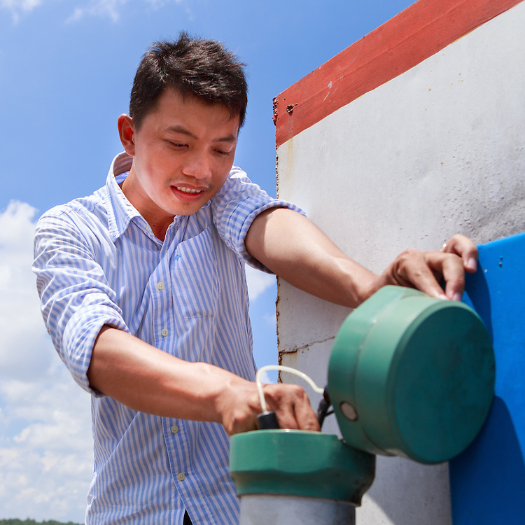 CAPTION: Mr Tro, a technician from the Centre of Environmental Monitoring (CEM), carries out a routine check on the salinity monitoring equipment. LOCATION: Salinity Monitoring Station # 2, Can Tho, Vietnam. INDIVIDUAL(S) PHOTOGRAPHED: Quach Van Tro, CEM technical staff.