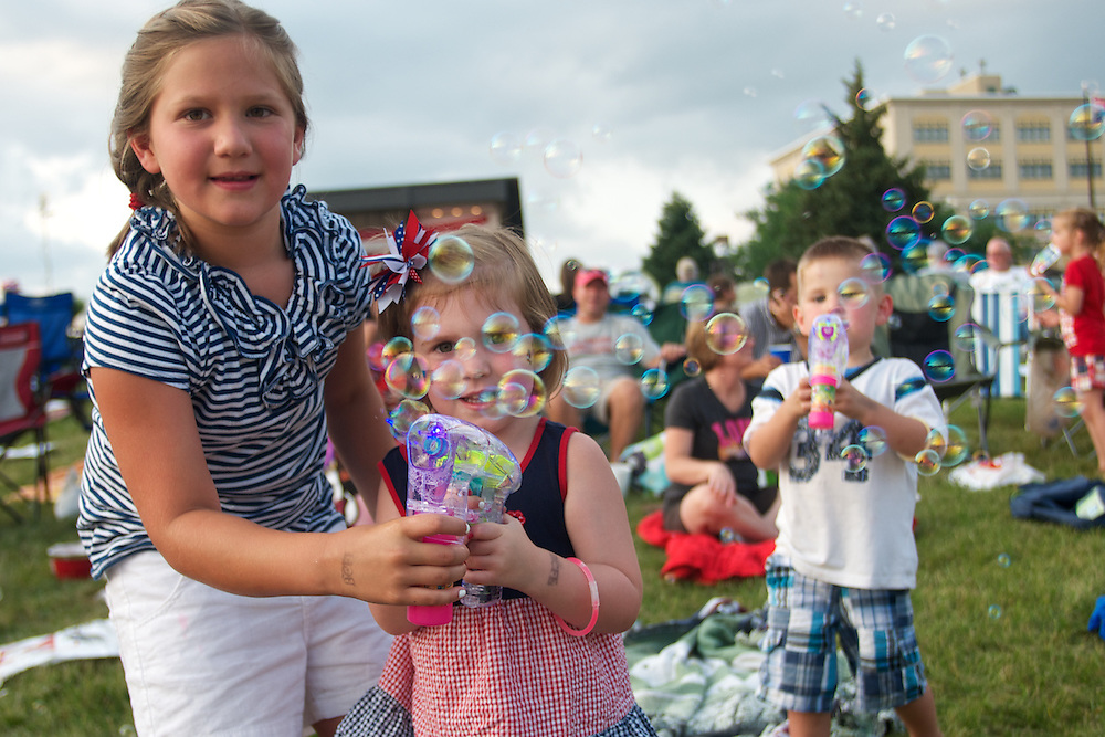 Molly Pitcher(right), 7, Ella Kokaly(center), 4, and Jagger Connelly (left), 3, play with bubble guns during the 2011 Bay City Fireworks Festival.     Lathan Goumas | The Bay City Times