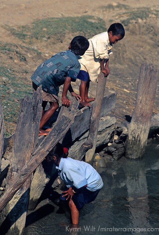 Asia, Nepal, Bardia. Kids playing at water's edge in Bardia, Nepal.