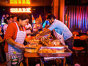 11 SEPTEMBER 2013 - BANGKOK, THAILAND:  Workers at the Shark, a go-go bar on Soi Cowboy, one of the red light districts in Bangkok, Thailand, carve barbecued piglets for a customer appreciation barbecue. Soi Cowboy, along with Nana Entertainment District and Patpong, are the districts that first brought Bangkok fame as a sex tourism destination. The areas got their start during the 1960's when American servicemen serving in Vietnam came to Thailand on R&R.   PHOTO BY JACK KURTZ