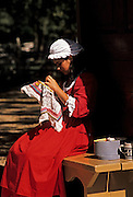 Image of a woman reenactor embroidering on Duke of Gloucester Street in Colonial Williamsburg, Virginia, east coast
