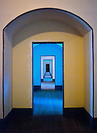 Yellow and blue light illuminates a long series of doorways at Fort Point, San Francisco