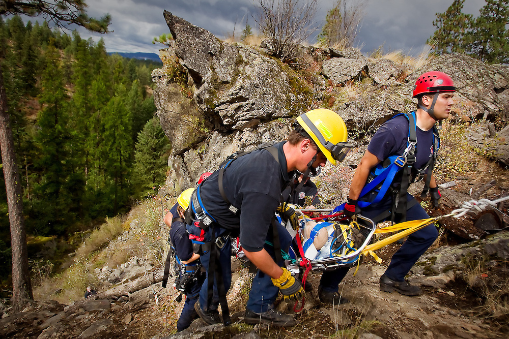 Kaipo Kuehu, right, and Brooks Brown, both firefighters with Kootenai County Fire & Rescue, finish climbing up a steep trail at Q'emiln Park in Post Falls with a rescue dummy during a high angle technical rescue training exercise Monday. The training involved hiking into a remote location to access a patient, setting up a rope system for access, and stabilize and transport the patient.