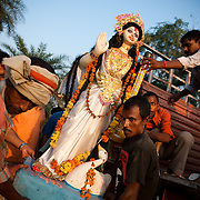 Worshipers unload an idol of the Hindu goddess Saraswati from a truck during celebration of Durga Puja festival, some 40km from the Indian capital of New Delhi, September 2009