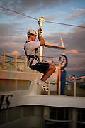 A passenger tries the zipline, one of the many activities offered onboard the cruise ship Oasis of the Seas. The ship, currently the largest in the world, is owned by Royal Carribean Cruise Line.