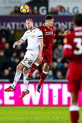 Mike van der Hoorn of Swansea City and Roberto Firmino of Liverpool compete for the ball - Rogan/JMP - 22/01/2018 - FOOTBALL - Liberty Stadium - Swansea, Wales - Swansea City v Liverpool - Premier League.