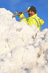 © Licensed to London News Pictures. 18/01/2018. Howgill Fells, UK. A workman smiles as he clears snow near the M6 this morning hotel after heavy overnight snow. Photo credit: John France/LNP