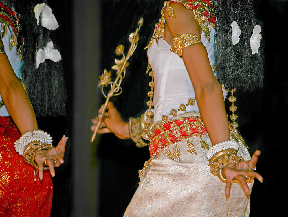Apsara dancers perform at a Siem Reap restaurant and night club. Closeup of gesturing hands, elaborate costume, bracelets, and hair ornaments.