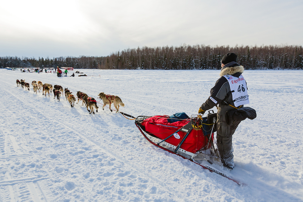 Musher Michael Williams Jr. competing in the 41st Iditarod Trail Sled Dog Race on Long Lake after leaving the Willow Lake area at the restart in Southcentral Alaska.  Afternoon.