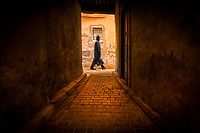 A man walks past an alley in the city of Fes, Morocco.