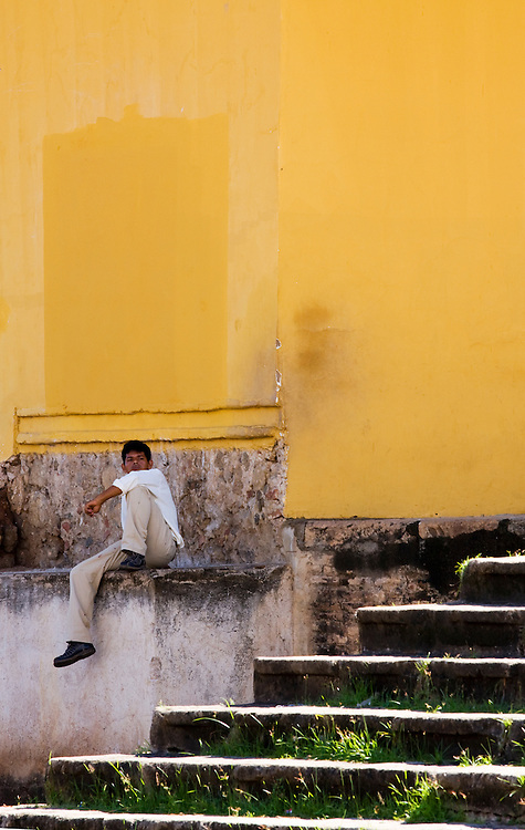 A man sits outside a brightly painted wall in Granada, Nicaragua.