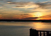 A spectacular sunset on Jekyll Island Georgia over the Savanah grasslands and intracoastal waterway with seabirds silhouetted on a dock.