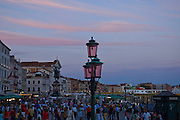 Crowds along the Grand Canal at dusk on a summer evening in Venice, Italy. Pink clouds, shich match the pink streetlamps,  foretell beautiful weather.