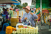 05 MAY 2013 - BANGKOK, THAILAND: A vendor sells flower garlands in front of the City Pillar during an unseasonal thunderstorm near the Grand Palace in Bangkok, Thailand. The rainy season in Bangkok is usually mid June through early November, but 2013 has seen unseasonal rains through what is normally Bangkok's dry season.       PHOTO BY JACK KURTZ