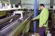 Machinist operating a knitting machine....