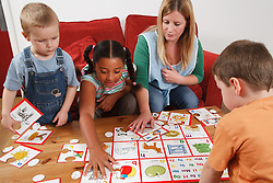 Nursery nurse doing a puzzle with children