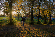 A cyclist pedals through an Autumnal park.
