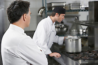Two male chefs working in kitchen