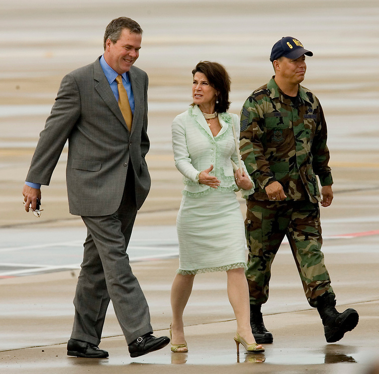 Congresswoman Katherine Harris, center, and Florida Gov. Jeb Bush, left are escorted to the flight line to wait for the arrival of President Bush at MacDill Air Force Base in Tampa, Fla. on Tuesday, May 9, 2006.(AP Photo/Scott Audette)