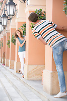 Tourist couple playing hide-and-seek amongst columns
