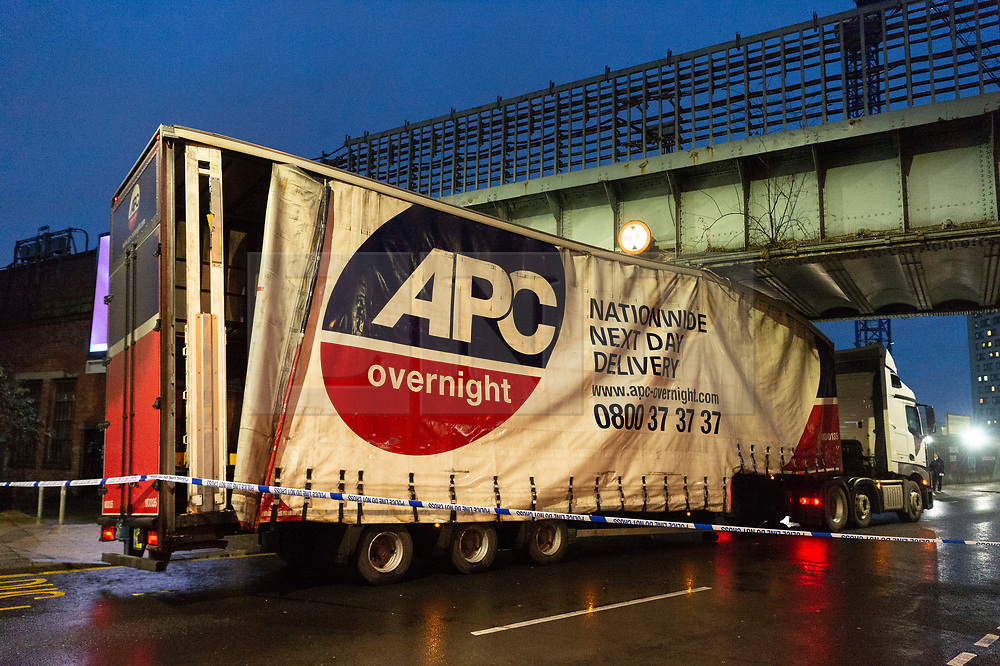 © Licensed to London News Pictures. 17/12/2019. London, UK. A HGV truck gets stuck under an overhead underground bridge outside Alperton tube station on Ealing Road. The roof of the truck is crushed as it appears too tall for the maximum height go the bridge. Police have closed off the accident scene. Photo credit: Ray Tang/LNP