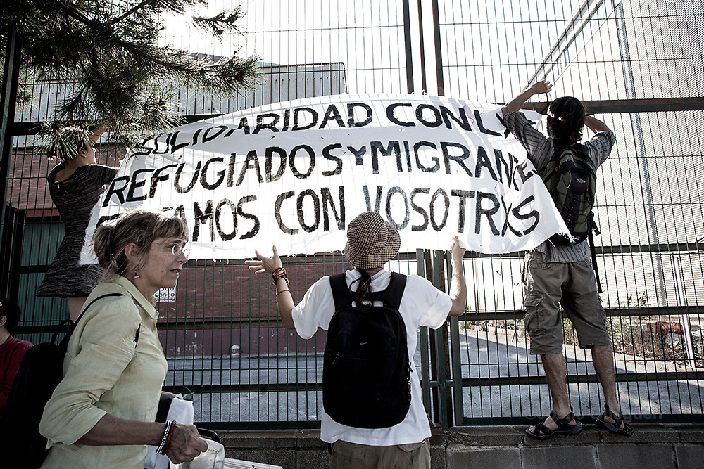 "Protesters put up posters during the march organized by""Tancarem el CIE"" to get to government to close the Immigration detention center permanently.   Barcelona 20/06/2015"