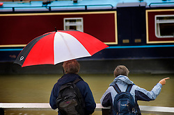 Visitors watch the boats in wet weather at Foxton Locks on the Grand Union Canal, Leicestershire, England, Europe, UK.