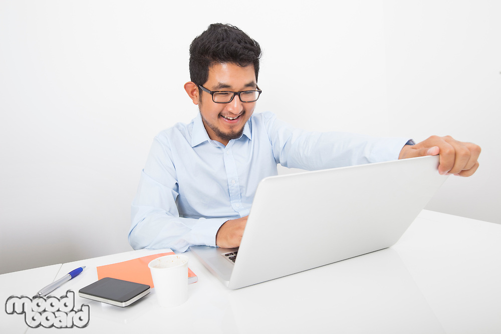 Smiling businessman working on laptop at desk in office