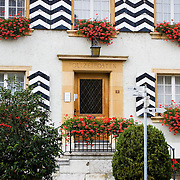 Black and white shutters and window boxes with red flowers decorate police station in Murten, Switzerland<br />