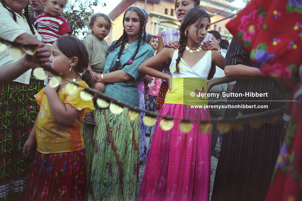 Roma girls and women watch as the gold of the Tomita family is brought out for public show, on the road outside their house, on the day of the baptism of Sarion Bratu Badea. The family gold was shown for a few minutes before being taken back to its hiding place.