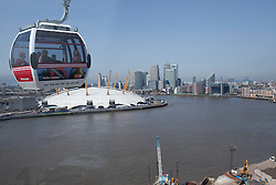 © Licensed to London News Pictures. 28/06/2012. LONDON, UK. An Emirates Air-Line cabin is seen with the O2 Dome and Canary Wharf beyond at the launch of London's first cable car system today (28/06/12). The new cable car system, running across the River Thames between the Greenwich Peninsula and the Royal Docks in East London, was today opened to the public, despite fears that it would not be ready in time for the London 2012 Olympics. Photo credit: Matt Cetti-Roberts/LNP