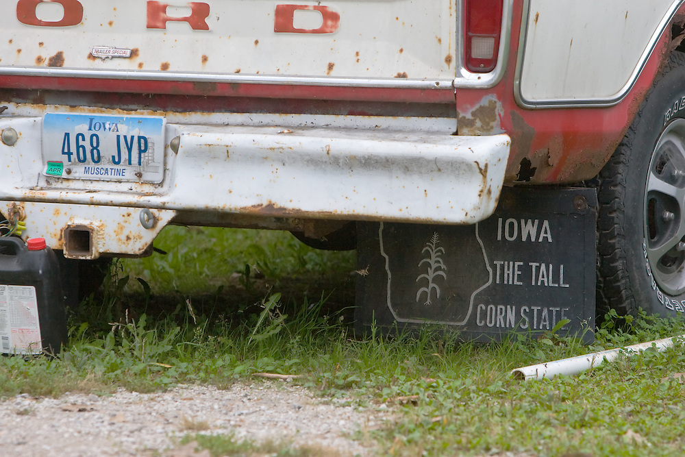 An old pickup truck parked in Muscatine, IA, a Mississippi River town, displays mud flaps with some Iowa pride.