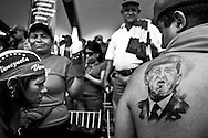 A supporter of the government show his tattoo with Hugo Chavez, the president of Venezuela and leader of Bolivarian revolution at a rally to commemorate the first anniversary of Hugo Chavez death