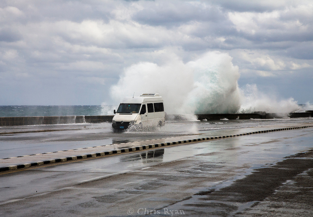 Van driving through flooded street while waves crash against the malecon during storm, Havana, Cuba