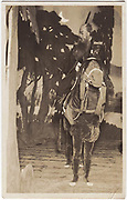 Kabuki actor siting atop two actors dressed in a horse costume and their feet visible, 1920s, silver gelatin bromide.<br />