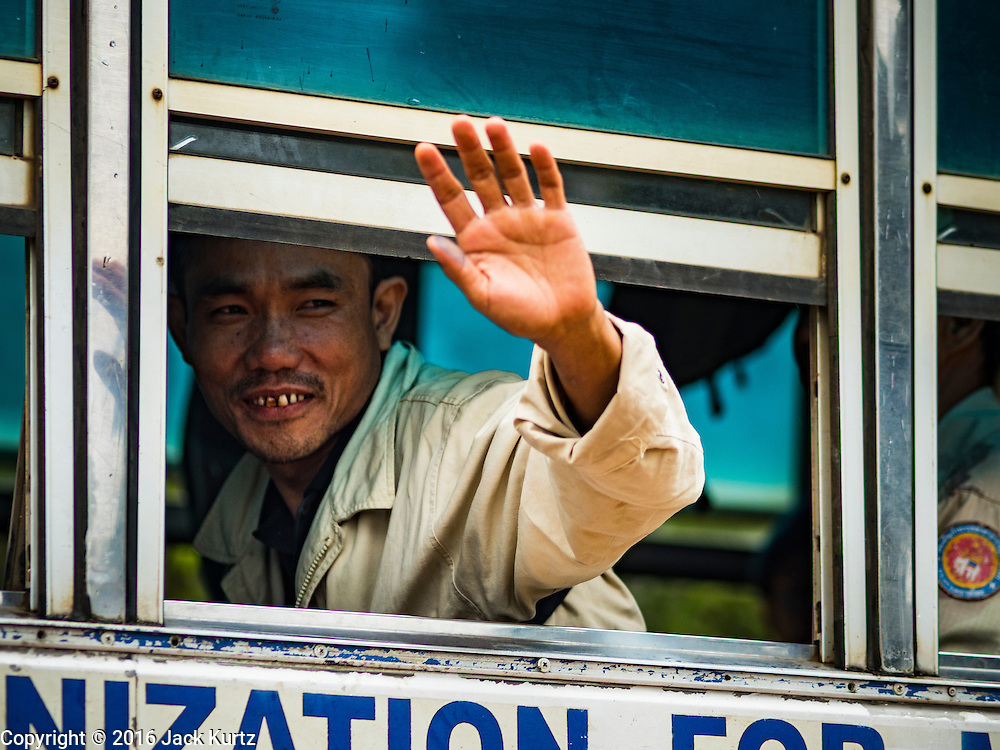 26 OCTOBER 2016 - NUPO TEMPORARY SHELTER, MAE CHAN, TAK, THAILAND:  A Burmese man waves as he leaves the the Nupo Temporary Shelter refugee camp during his repatriation. Sixtyfive Burmese refugees living in the Nupo Temporary Shelter refugee camp in Tak Province of Thailand were voluntarily repatriated to Myanmar. About 11,000 people live in the camp. The repatriation was the first large scale repatriation of Myanmar refugees living in Thailand. Government officials on both sides of the Thai / Myanmar border said the repatriation was made possible by recent democratic reforms in Myanmar. There are approximately 150,000 Burmese refugees living in camps along the Thai / Myanmar border. The Thai government has expressed interest several times in the last two years in starting the process of repatriating the refugees.    PHOTO BY JACK KURTZ