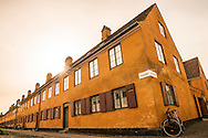 A wide-angle photograph of stunning orange architecture in Copenhagen set against the backdrop of a setting sun.