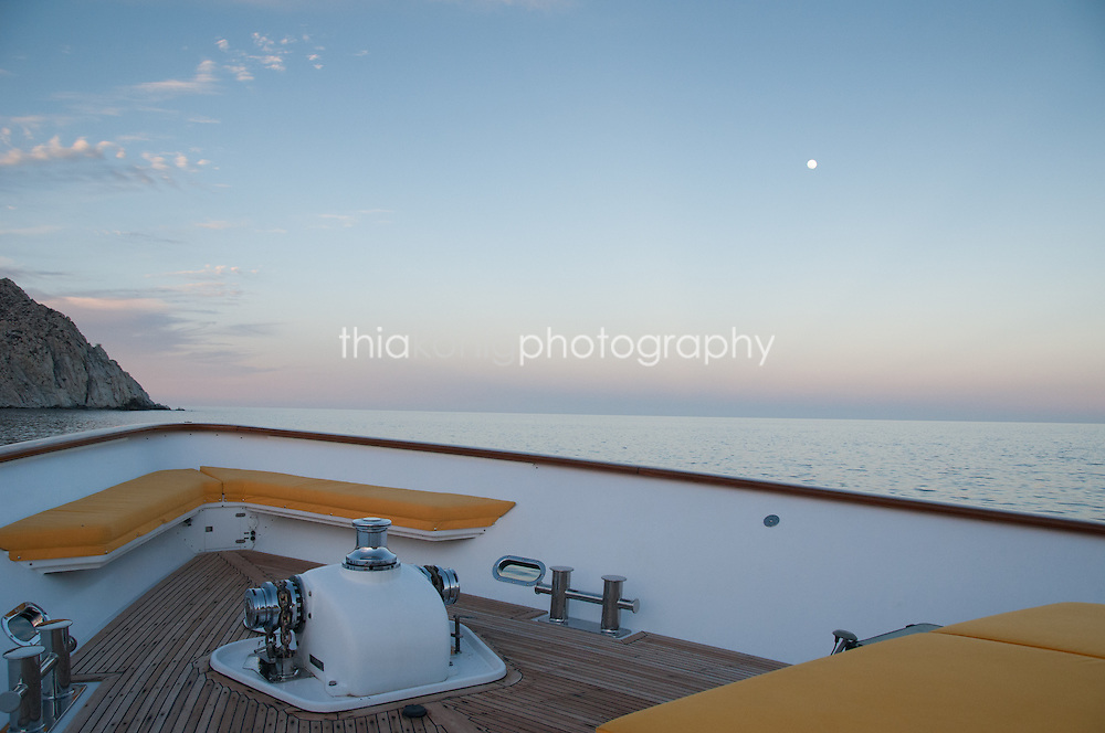 View of the bow of a yacht to ocean view with full moon and twilight sky, Sea of Cortez, Mexico.