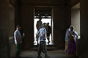 Tourists looking around and examining inside the ancient temple of Angkor Wat, Krong Siem Reap, Cambodia. Angkor Wat is a temple complex in Cambodia and the largest religious monument in the world, with the site measuring 162.6 hectares. It is Cambodia's main tourist destination.  (photo by Andrew Aitchison / In pictures via Getty Images)