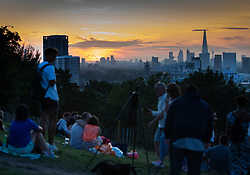 © Licensed to London News Pictures. 23/08/2019. London, UK. People gather in Greenwich Park as the sun sets over the London skyline after a hot August day. Record high temperatures are expected in parts of the United Kingdom over the three day bank holiday weekend. Photo credit: Peter Macdiarmid/LNP