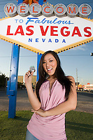 Woman posing in front of Las Vegas welcome sign, Nevada, USA